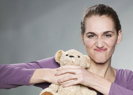 strangling: irritated young woman strangling her teddy bear for jealousy or teenager crisis Stock Photo