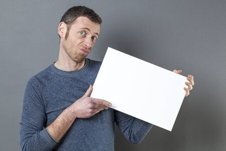 dubious: dubious 40s man holding a blank banner for doubt or surprising advertising Stock Photo
