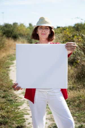teasing: summer outdoors teasing - gorgeous 50s woman with casual hat holding a white blank sign to write message on board,walking on path in summer grass field