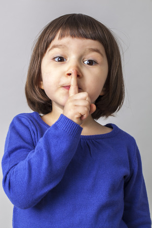 wanting: funny preschool girl wanting to keep silent with her finger on lips