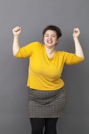 donne obese: il concetto di successo - estroversa ragazza sovrappeso che indossa un maglione giallo che esprime il suo successo e la gioia nella danza Archivio Fotografico