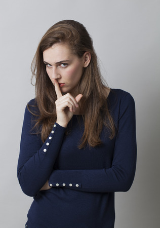 cautious: secret and taboo concept - severe 20s girl with long hair wearing navy blue sweater asking for silence with finger on mouth,studio shot Stock Photo