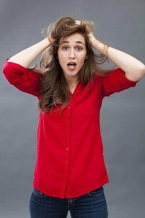 decepci�n: sorpresa y decepci�n concepto - retrato de mujer morena l�o de un 20 sonriendo hasta su pelo expresar confusi�n para el asombro, tiro del estudio