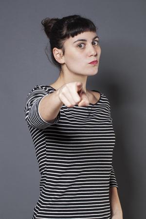 firmness: grave joven mujer morena mirando a alguien con el dedo �ndice hacia adelante acusando y condescendiente alguien con firmeza Foto de archivo