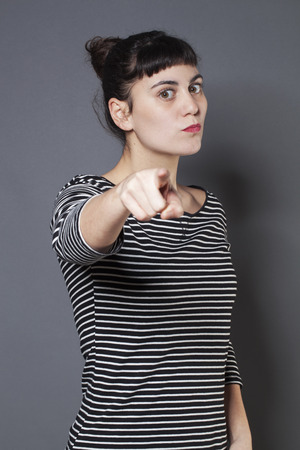 firmness: severe young brunette woman staring at someone with index finger forward accusing and patronizing someone with firmness