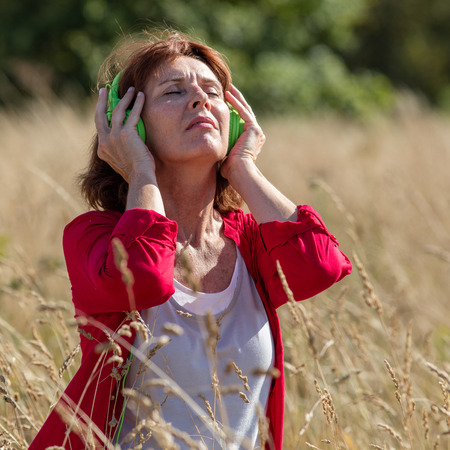 quietness: outdoors music - relaxed 50s woman listening to music with headphones alone in long summer grass field,enjoying some quietness