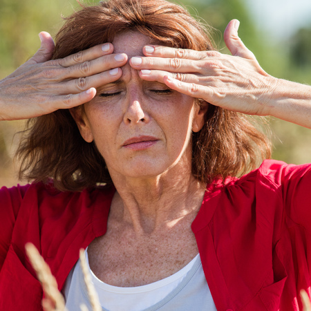 soothing: Hay fever allergies - beautiful mature woman with sinus pain massaging her forehead for headache soothing in dry meadow,natural summer daylight Stock Photo