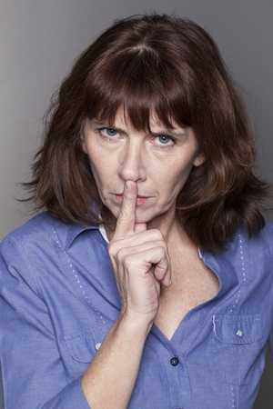taboo: secret and taboo concept - severe 50s woman wearing blue shirt asking for silence with finger on mouth,studio shot