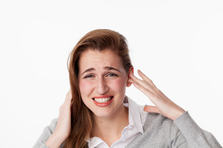 scowl: tinnitus concept - frowning young woman having painful migraine,covering closed ears,annoyed by loud noise not wanting to hear their side of story