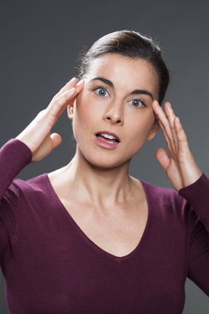 acupressure hands: surprised 30s woman smiling in practising face acupressure with hands on face and temples for natural eye care and facial contour exercise Stock Photo