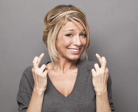 nervousness: success concept - pouting 30s blond woman double crossing her fingers with anxiety and fun for victory and ambition Stock Photo