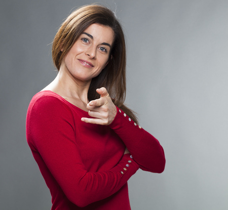 30s: satisfaction and smile concept - happy 30s businesswoman with arms crossed,pointing her fingers for seduction and happiness at her position Stock Photo