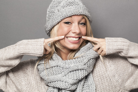 fake smile: hypocrisy concept - winter 30s blond woman with a fake smile expressing artificial comfort to show hypocritical success or winter wellbeing with warm clothing Stock Photo