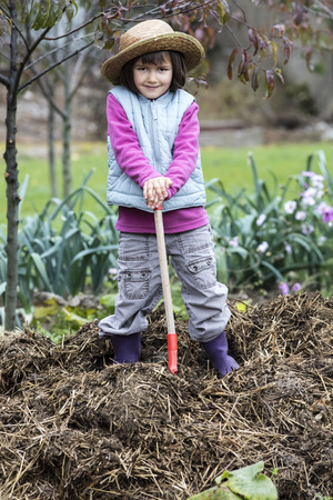 vegetable garden: kid gardening concept - thrilled child posing with a shovel on top of a pile of manure in home vegetable garden and straw hat on in autumn season, outdoors view