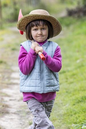 autonomia: Concepto de jardinería niño - determinó 4 años de edad, el niño que recorre con una pala en el hombro y el sombrero de paja en, pasando el jardín o jugar en el jardín, al aire libre vista