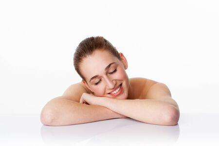 mimos: sonriendo modelo de mujer joven con los ojos cerrados despu�s de un masaje, con los brazos cruzados sobre el vidrio blanco para cuidar en exceso de relajaci�n fresca, tiro del estudio, fondo blanco Foto de archivo