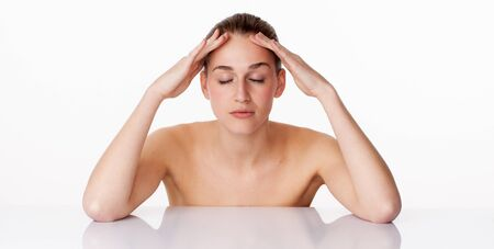 pampering: relaxed young female model with eyes closed massaging her face,leaning on white glass for lifting pampering treatment,studio shot,white background