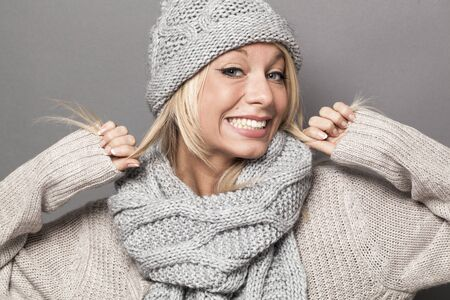hypocritical: hypocrisy concept - winter 30s blond woman with a fake smile expressing artificial feelings to show hypocritical success or winter comfort with warm clothing