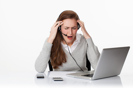 temper: stress at work concept - desperate young female office executive working in sparse office environment,loosing temper on headset,studio shot,white background