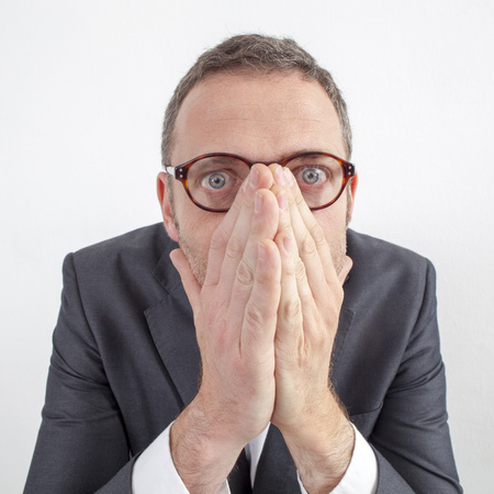 taboo: expressive corporate man concept - scared middle age businessman hiding his mouth with hands for management taboo for humor,wide angle on white background Stock Photo