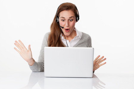 unexpected: fun at work concept - excited young female manager winning unexpected business with headset on and computer on desk, studio shot,white background