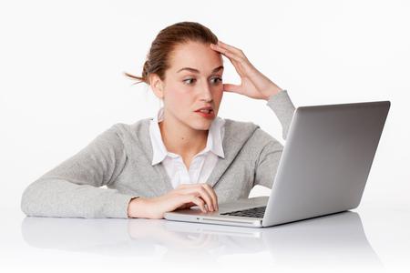 nerveux: problèmes au concept de travail - jeune étudiante nerveux ou employé de bureau penser dans un environnement de bureau pur, travaillant sur ordinateur, tourné en studio, fond blanc