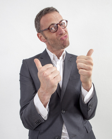 hand  up: expressive corporate man concept - happy middle age businessman expressing energy and success with with double thumbs up,wide angle on white background