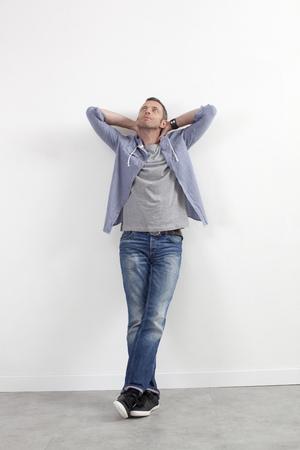 relajado: expresivo concepto de hombre casual - relajó hombre de mediana edad de pie contra la pared blanca con los brazos extendidos expresando imaginación, fondo blanco