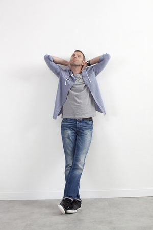 arms behind head: expressive casual man concept - relaxed middle age man standing against white wall with outstretched arms expressing imagination,white background