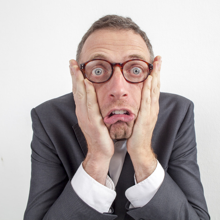 expressive corporate man concept - shocked middle age businessman expressing surprise and disappointment with humor,wide angle on white background