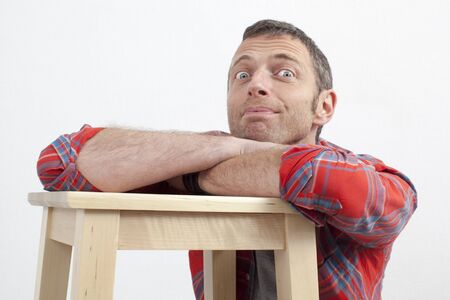 checked shirt: expressive casual man concept - cheerful middle age man with checked shirt leaning on wooden stool expressing excitement and happiness,white background Stock Photo