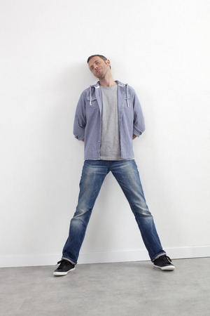 arms behind head: expressive casual man concept - thinking middle age man standing against white wall with body language expressing wellbeing,white background