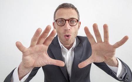 wacky: expressive corporate man concept - weird middle age businessman playing with his hands,hypnotizing or manipulating,wide angle on white background