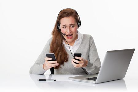 estrés en el concepto de trabajo - pánico ejecutivo de la Oficina mujeres jóvenes la búsqueda de soluciones desesperadas en el auricular con dos teléfonos, tiro del estudio, fondo blanco