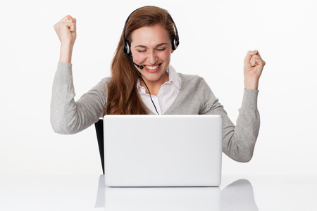 fun at work concept - winning young female manager winning business with headset on and computer on desk, studio shot,white background Фото со стока