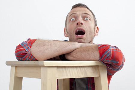 boca abierta: expresiva hombre casual concepto - hombre de mediana edad sin habla con camisa a cuadros que se inclina en taburete de madera que expresa miedo y la sorpresa, el fondo blanco