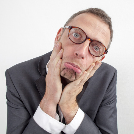 making a face: expressive corporate man concept - upset middle age businessman making a face,pressing his cheeks with both hands down,wide angle on white background