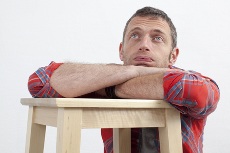 checked shirt: expressive casual man concept - lazy middle age man with checked shirt leaning on wooden stool expressing depression and frustration,white background