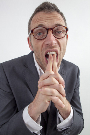 resignation: expressive corporate man concept - dubious middle age businessman with eyeglasses biting his fingers from management resignation or leadership frustration,wide angle on white background