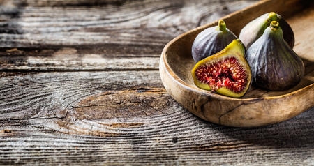 stilllife: fruit still-life - ripe figs whose one is cut in half in old wood tray on wooden background for genuine texture effect and food freshness
