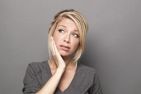 confundido: la duda y la preocupaci�n concepto - 20s confusas mujer rubia linda en busca de ideas o soluciones con la mano que toca su cara para el reaseguro, fondo gris