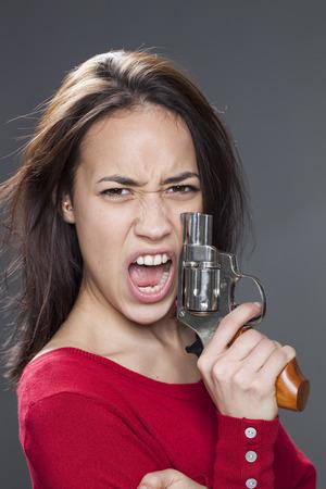 venganza: femenina concepto de energía - 20s furiosos chica multiétnica gritando en la celebración de un arma de venganza contra la agresión y la violencia
