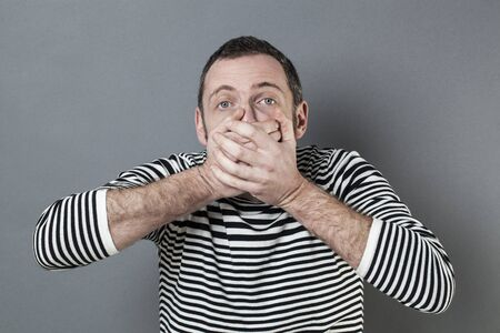 regret: mistake concept - stunned middle age man with striped sweater holding his mouth tight with his hands expressing regret and amazement