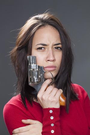 venganza: Concepto de la potencia femenina - el ceño fruncido de la muchacha multiétnica atractiva que muestra un arma de venganza o la lucha contra el abuso