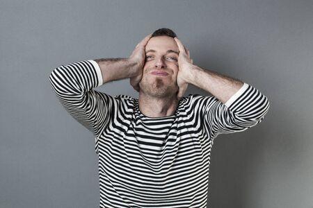 desilusion: Concepto de error - sonriente hombre de mediana edad con una perilla estresando y expresando su decepción con las manos sosteniendo la cabeza, fondo gris estudio