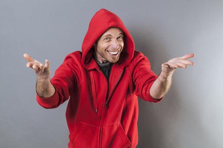adolescencia: masculina concepto de la adolescencia - sonriendo mediana edad que llevaba una capucha rapero su�ter rojo que juega con la diversi�n gesto de la mano, estudio