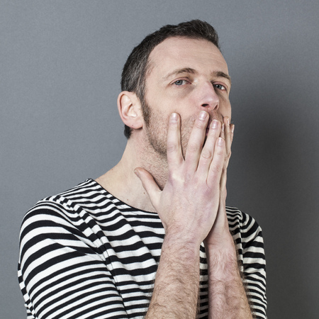 misunderstanding: doubt and reflection concept - portrait of stressed out 40s man looking concerned with hands hiding his mouth for misunderstanding,grey background Stock Photo