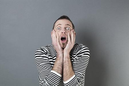 decepci�n: Concepto de error - sorprendi� hombre de mediana edad con una perilla estresando y expresando su decepci�n con las manos tocando la cara, fondo gris estudio