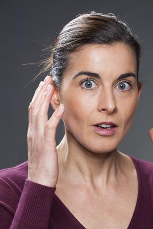 interrogativa: la duda y el concepto de la sorpresa - hermosas 30s mujer con los ojos bien abiertos expresando sorpresa con la cara y las manos arriba, fondo gris Foto de archivo
