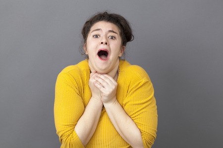 extrovert: praying concept - excited big 20s woman suffocating,begging with both hands tight on her chest,getting a good or bad shocking news